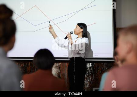 Seitenansicht Porträt des zeitgenössischen Geschäftsfrau, Präsentation auf graph Linien auf Leinwand während der Vorlesung zeigen, kopieren Raum - Stockfoto