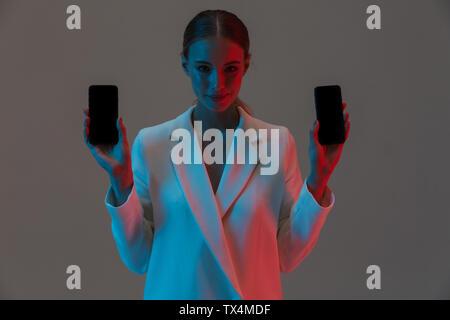 Bild Nahaufnahme von stilvolle Frau 20 s mit zwei Handys und zeigt schwarze Bildschirme beim Stehen unter Neonlicht isoliert über grauer Hintergrund - Stockfoto