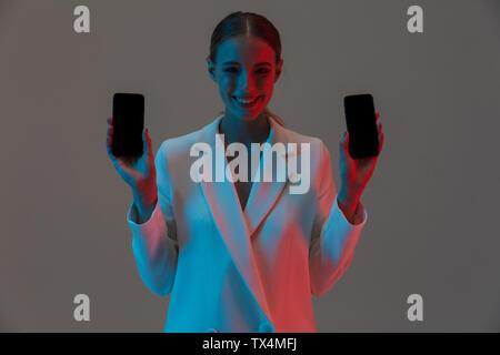 Bild Nahaufnahme von Pretty Woman 20 s mit zwei Handys und zeigt schwarze Bildschirme beim Stehen unter Neonlicht isoliert über grauer Hintergrund - Stockfoto