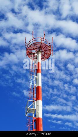 Telecom Tower für die drahtlose Übertragung von Radio, Handy oder Internet Signal. Telecom Mast in Rot und Weiß mit blauen Himmel und Wolken bemalt - Stockfoto