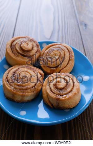Brötchen mit curl mit Zimt und Zucker auf einem blauen Polka Dot platte Holz- Hintergrund. Frühstück. Hausgemachte frische Backwaren. Bäckerei, Backwaren. Schließen - Stockfoto