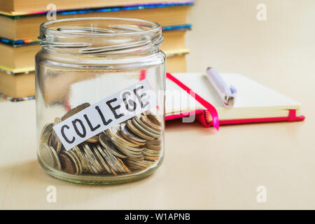 Eine Menge Münzen und College Wort in einem Glas in der Nähe eines weißen Kugelschreiber und einige Bücher auf einem Tisch. Geld sparen für Hochschule und Bildung Konzept. Pl - Stockfoto