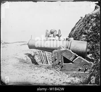 Große Pistolen in der Nähe von Ft. Sumter, S. C. Die Vordergrund Waffe ist ein 10-Zoll Modell 1844 columbiad, gebändert und geplündert, die vor kurzem von der Union am Fort Johnson in Charleston Harbor erfasst. Der Schlitten hat durch die von den Eidgenossen geschnitten worden mit der Waffe an die Union zu verweigern. - Stockfoto