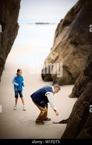 Mann beugt sich über einen Zweig der seawood in einer sandigen Bucht zu pflücken, wie seine junge Tochter nervös Uhren. - Stockfoto