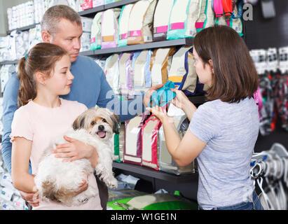 Junge Familie mit jugendlichen Tochter besuchen Pet Shop auf der Suche nach Zubehör für Ihren Hund - Stockfoto