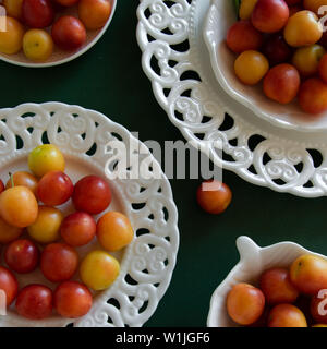 Organische frische Pflaumen in Weiß vintage Platten auf tiefen grünen Hintergrund. Gesunde vegetarische Nahrung. Stillleben mit Platz für Text - Stockfoto