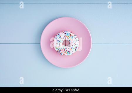 Eine weiße Donut oder Krapfen in einem rosa Platte auf einem Pastell-blaue Holztisch Hintergrund. Ansicht von oben. - Stockfoto