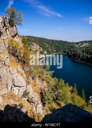 Ansicht der Rückseite des Frauen Wanderer mit Blick auf den Wald von Hans rock Kante über dem Lac Blanc Rocher Hans, Frankreich - Stockfoto