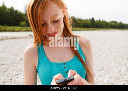 Junge Frau mit einem Mobiltelefon an der Isar, München, Bayern, Deutschland - Stockfoto