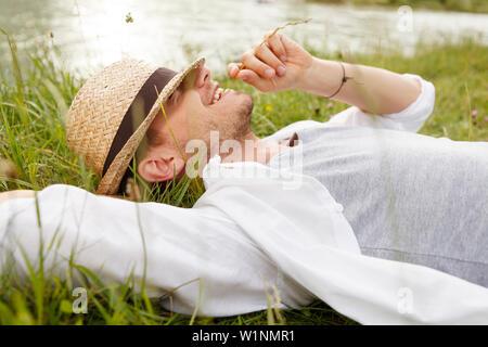 Junger Mann auf der Isar riverbank, München, Bayern, Deutschland - Stockfoto