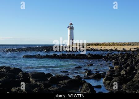 Blick über schwarzen Felsen zu den Weißen Port Fairy Leuchtturm am Rande des Südlichen Ozeans - Stockfoto