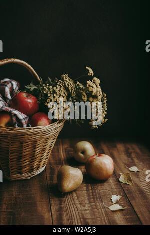 Herbst Komposition mit gelben Rainfarn Blüten und Äpfel in einem Weidenkorb und Birnen auf einem hölzernen Hintergrund - Stockfoto