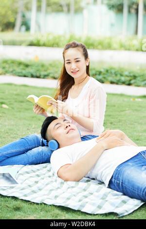 Portrait von jungen asiatischen Frau lächelnd in die Kamera während der Sitzung auf dem Gras. Sie ist ein Buch lesen mit jungen Mann lag auf den Knien und hören auf m - Stockfoto