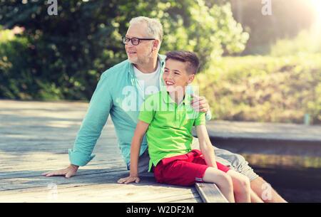 Großvater und Enkel sitzen am Fluss Liegeplatz - Stockfoto