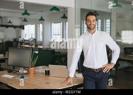 Lächelnde junge Unternehmer lehnte sich gegen eine Tabelle in einem Büro - Stockfoto