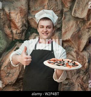 Fröhlicher Koch hält eine große Pizza und zeigt einen Daumen nach oben. - Stockfoto