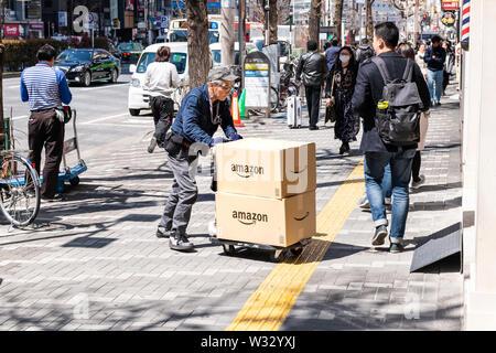 Tokio, Japan - April 4, 2019: Ältere alte Delivery Man dolly voranzutreiben, die Bereitstellung von Amazon boxen Pakete in Shinjuku auf der Straße Bürgersteig - Stockfoto