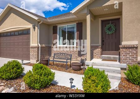 Haus mit einer Mischung aus Beton und Mauerwerk gegen den blauen Himmel mit Wolken. Gartenbank, Garagentor, Haustür, und Fenster mit Rollläden können auch sein - Stockfoto