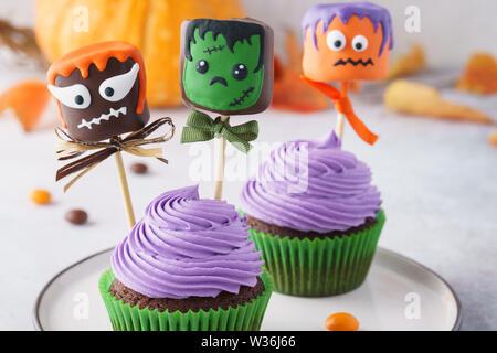 Eine Nahaufnahme der festlichen Halloween Cupcakes mit farbigen Dekorationen. Marshmallow in Schokolade mit gruseligen Monstern. Selektive konzentrieren. - Stockfoto