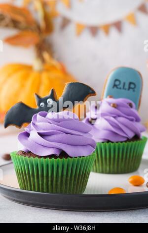 Eine Nahaufnahme der festlichen Halloween Cupcakes mit gruseligen Lebkuchen cookies als bat und Tombstone geformte eingerichtet. Hellen Hintergrund, selektive konzentrieren. - Stockfoto
