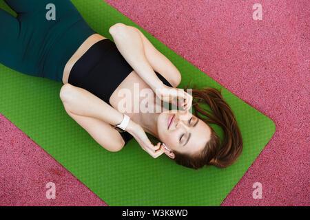 Foto von oben von der hübschen Sportlerin 20 s tragen Trainingsanzug und earpods liegen auf Fitness Matte während des Trainings am Sportplatz - Stockfoto