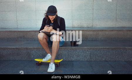 Sitzender junger Mann mit einem Laptop auf dem Schoß ist Kontrolle ein Smartphone. Eine gelbe Skate steht zu seinen Füßen. Platz kopieren - Stockfoto