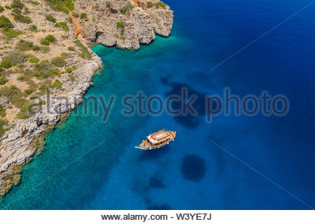 Antenne Drohne auf einem traditionellen Holzboot auf einem Crystal Clear Blue Ocean (Kreta, Griechenland) - Stockfoto