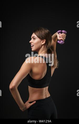 Attraktive lächelnden Jungen gesunde Fitness Frau mit Sport-BH und Shorts über schwarzen Hintergrund isoliert, das Training mit Kurzhanteln - Stockfoto