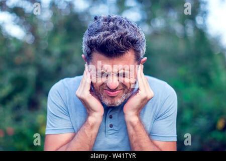 Unglückliche Menschen in Ohrenschmerzen berühren seine schmerzhaften Kopf outdoor - Stockfoto