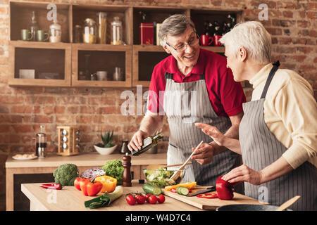 Älterer Mann und Frau lachend und Zubereitung von gesunder Nahrung in der Küche - Stockfoto