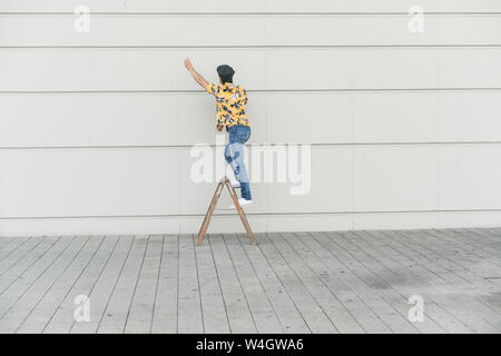 Junger Mann, der flache Hut und Aloa Shirt, stehend auf Schritt Leiter, das Berühren der Wand - Stockfoto