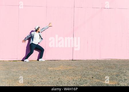 Junger Mann vor rosa Bau Barriere, Gefühl gefangen - Stockfoto
