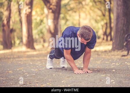 Jungen athletischen Mann tun Push-ups im Park, Vorbereiten für Morgen Workout. - Stockfoto