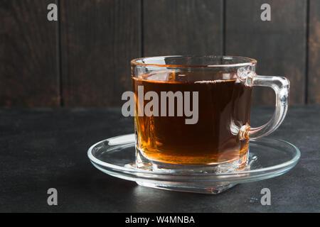 Ein Glas Tasse Aroma schwarzer Tee mit Untertasse über schwarzen Tisch aus Stein und Holz- wand. Kopieren Sie Platz. Selektiver Fokus - Stockfoto
