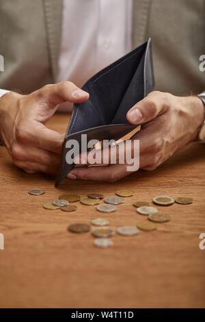 7/8-Ansicht des Menschen zeigen leere Mappe in der Nähe von Münzen auf hölzernen Tisch - Stockfoto