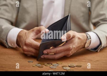 Teilansicht des Menschen zeigen leere Mappe in der Nähe von Münzen auf hölzernen Tisch - Stockfoto