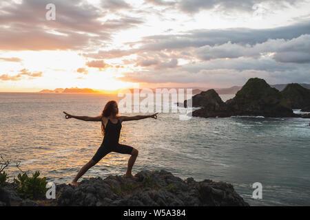 Junge schlanke Frau Yoga bei Sonnenuntergang mit schönen Meer- und Bergblick. Training im Freien, Sport und Wohlbefinden. Farbenfroh und majest - Stockfoto