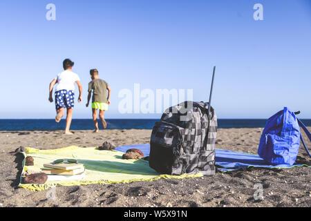 Studierenden, die gerne am Strand nach dem Ende der Schule. Fokus auf den Rucksack und Handtücher, zwei Jungs spielen auf dem Hintergrund Konzept der Freiheit ein - Stockfoto