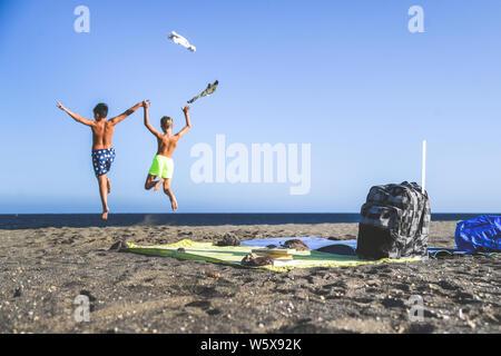 Studenten springen gerne am Strand nach dem Ende der Schule. Fokus auf den Rucksack und Handtücher, zwei Jungs spielen auf dem Hintergrund Konzept der Freiheit ein - Stockfoto