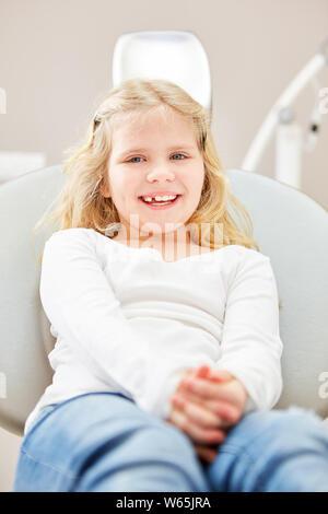 Glückliches Mädchen sitzt angstfrei beim Zahnarzt in den behandlungsstuhl vor der Prüfung - Stockfoto