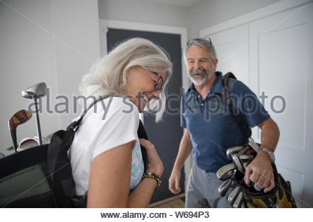 Gerne älteres Paar mit Golf Taschen leaving home - Stockfoto