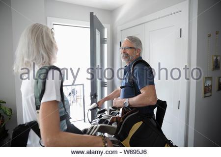 Senior Paar mit Golf Taschen leaving home - Stockfoto