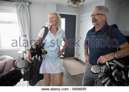 Senior Paar mit Golf Taschen im Wohnzimmer - Stockfoto