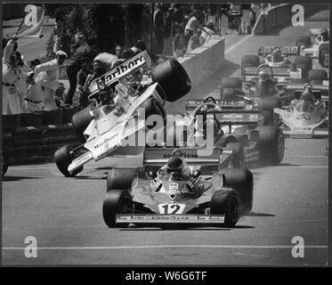 Uns Formel 1 Grand Prix, 1977, Long Beach Kalifornien mit der späten Driver James Hunt von England (gestorben 1993), World Champion F1 Fahren auf einem Rad nach der ersten Runde Unfall in der ersten Kurve Ecke mit 4 Rädern, Tyrell, hinter #12 Ferrari von Gilles Villeneuve (1982 gestorben) von Kanada, Sieger hatte von angetriebenen - Mario Andretti - Jagd war aus dem Rennen aus diesem Kontakt in seinem McLaren, aus original 8 x 10 Drucken scannen. James Simon Wallis Jagd war ein britischer Rennfahrer, der die Formel-1-Weltmeisterschaft 1976 gewann. Nach seinem Ausscheiden aus dem Rennsport 1979, Hunt wurde zu einem Medienkommentator und Busin - Stockfoto