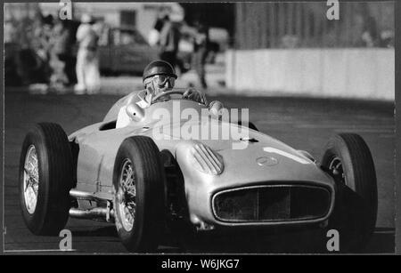 Juan Manuel Fangio, der den Spitznamen El Chueco oder El Maestro, fahren die Mercedes Benze W 196 an den US Grand Prix in Long Beach Kalifornien in den späten 70er Jahren, als er ein argentinischer Rennfahrer war. Er beherrschte die ersten zehn Jahre in der Formel 1 und gewann die Welt Meisterschaft fünfmal. Von Kindheit an, er brach seine Studien Automechaniker zu verfolgen - Stockfoto