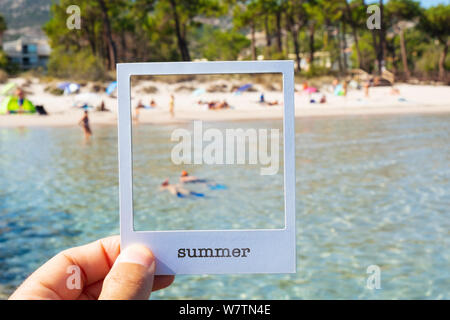Nahaufnahme von einem Mann mit einer weißen Pappe Rahmen, mit dem Wort Sommer geschrieben, Framing ein Strand mit unkenntlich Menschen, simuliert werden, um eine - Stockfoto