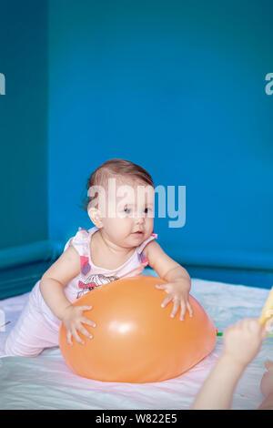 Baby spielt mit einem Ballon. Baby Mädchen ihre täglichen Aktivitäten zu tun. Kleine süße Mädchen lernen, aufzustehen und zu gehen. Platz kopieren - Stockfoto