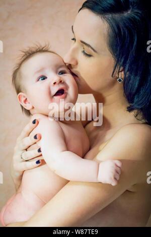 Junge schöne Mutter brünett ohne Kleidung ihre Arme halten und küssen Sie ihren kleinen Sohn. Glückliche Kindheit - Stockfoto