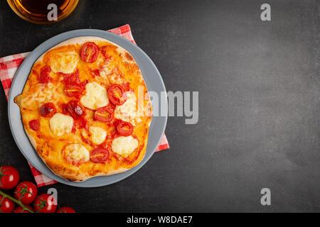 Hausgemachte Pizza Margarita mit Tomaten, Basilikum und Mozzarella auf grau Platte, Ansicht von oben - Stockfoto