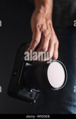 Nahaufnahme eines jungen kaukasischen Mann mit einer Spiegelreflexkamera in der Hand - Stockfoto